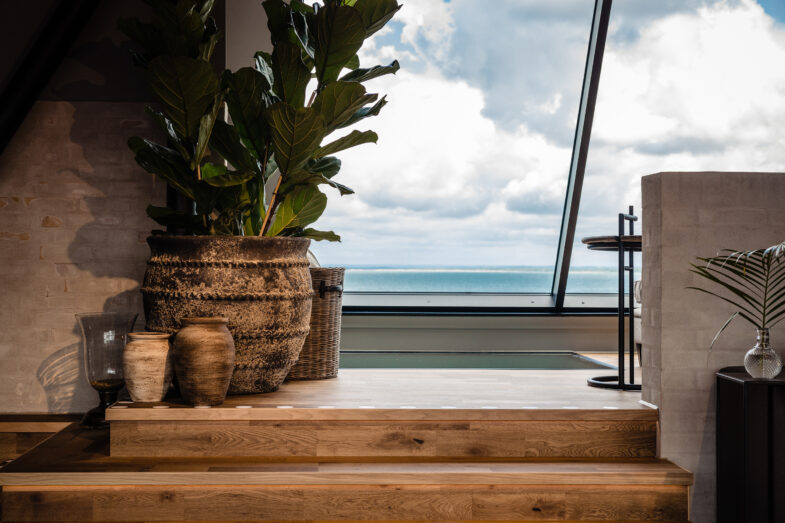 Inredning i relaxavdelning på rooftop spa med havet i bakgrunden.