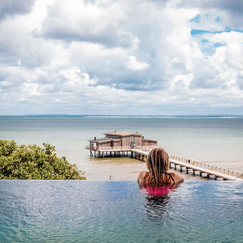 Kvinna i infinity pool på rooftop spa blickar ut över kallbadhus och hav.