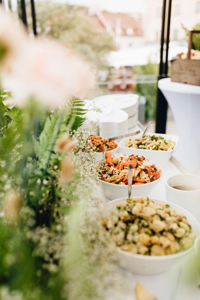 Buffébord med salladsskålar dekorerat med somriga blommor.