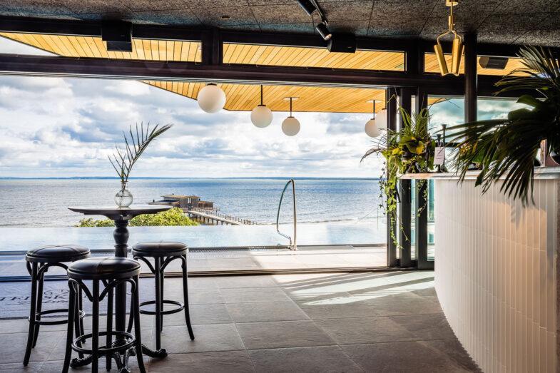 Bar och lounge i rooftop spa med hav i bakgrunden.