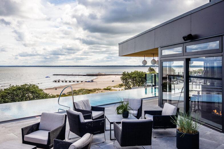 Fåtöljer på rooftop spa med hav och strand i bakgrunden.