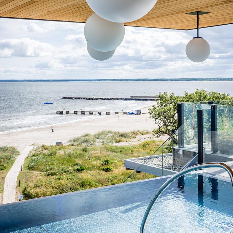 Infinity pool med utsikt över strand och hav i sommarväder.