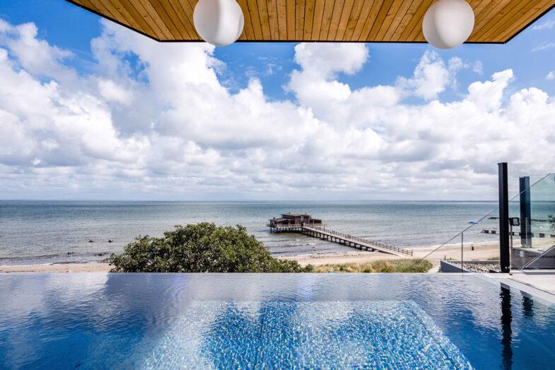 Infinitypool i solsken på rooftop spa med utsikt över strand och hav.
