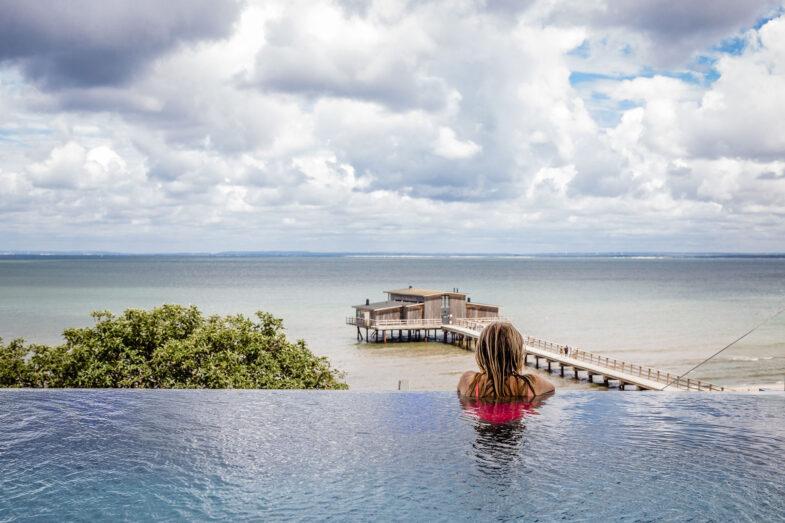 Kvinna i infinity pool blickar ut över hav och kallbadhus.