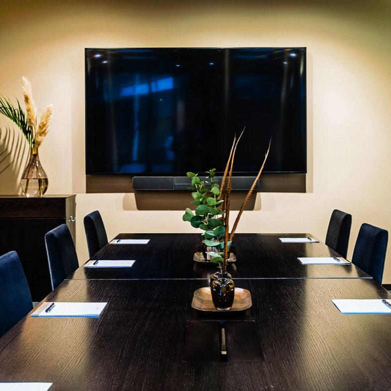 Konferenslokal med mötesbord och digital skärm.