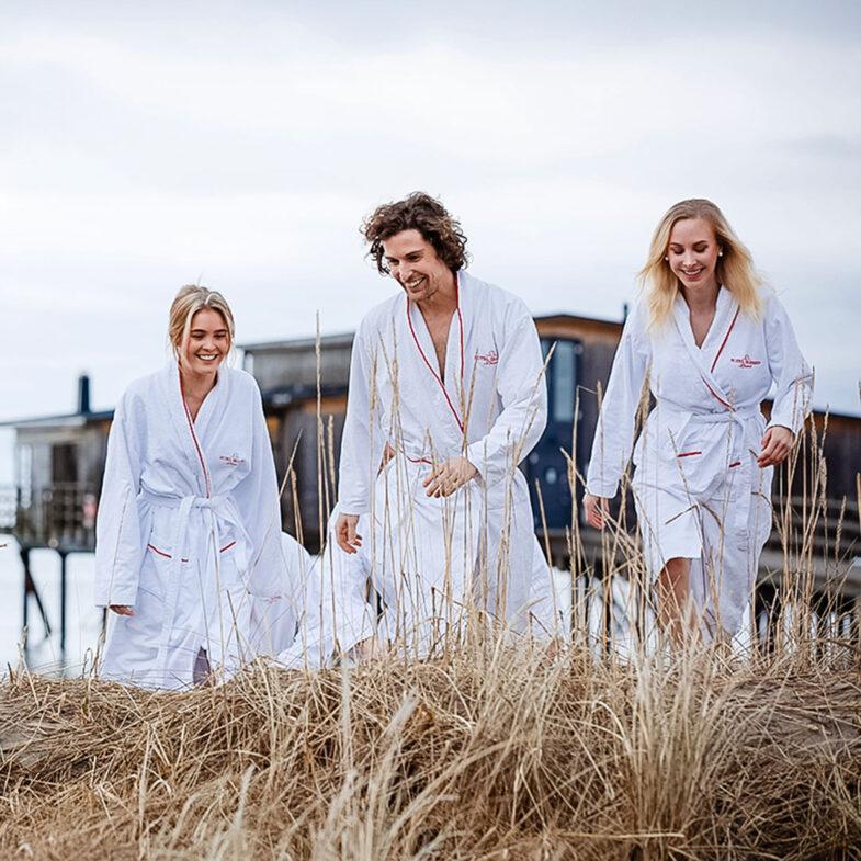 Tre personer i badrock på strand med kallbadhus i bakgrunden.
