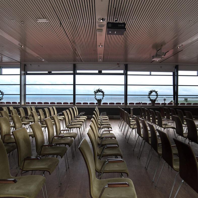 Större konferenslokal med havsutsikt möblerad i biosittning.