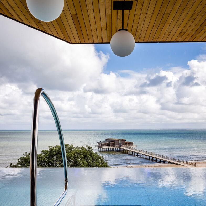 Vy över hav och kallbadhus från infinity pool.