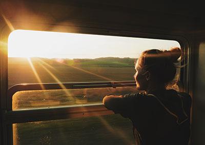 person som blickar ut över landskap och solnedgång från tågfönster.